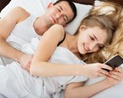 cheating woman laying in bed with sleeping husband while texting