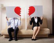 couple each holding half of a broken heart sign